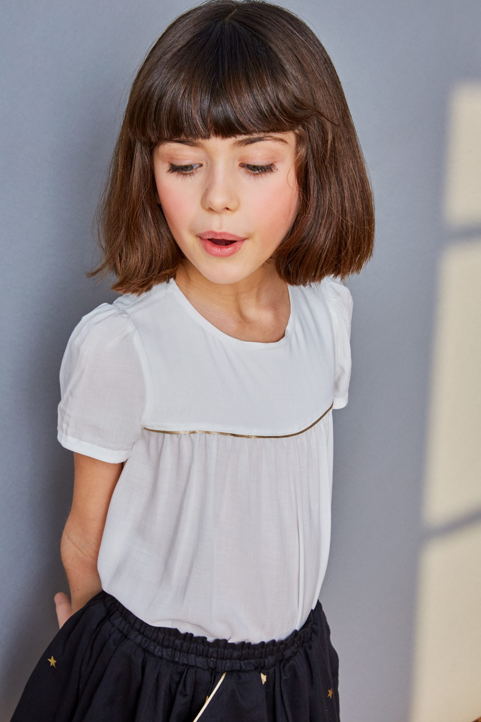 Girls short sleeve ivory blouse with gold piping