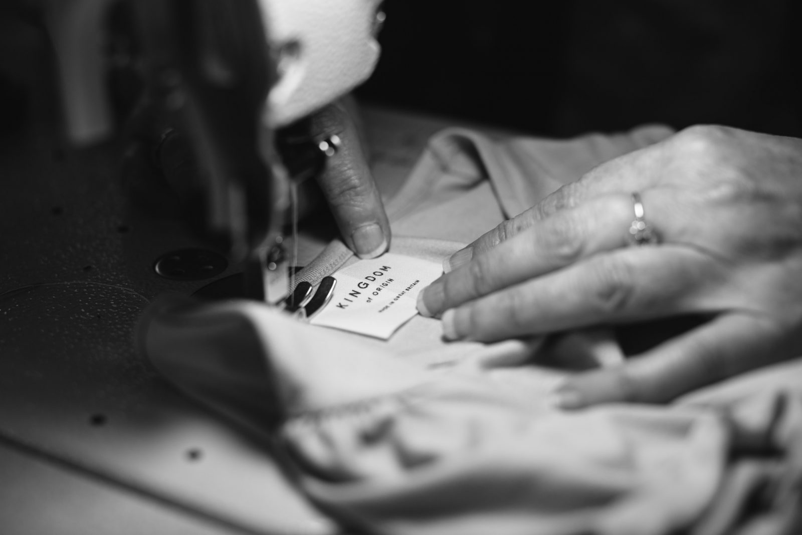 British seamstress sewing on a Kingdom of Origin label